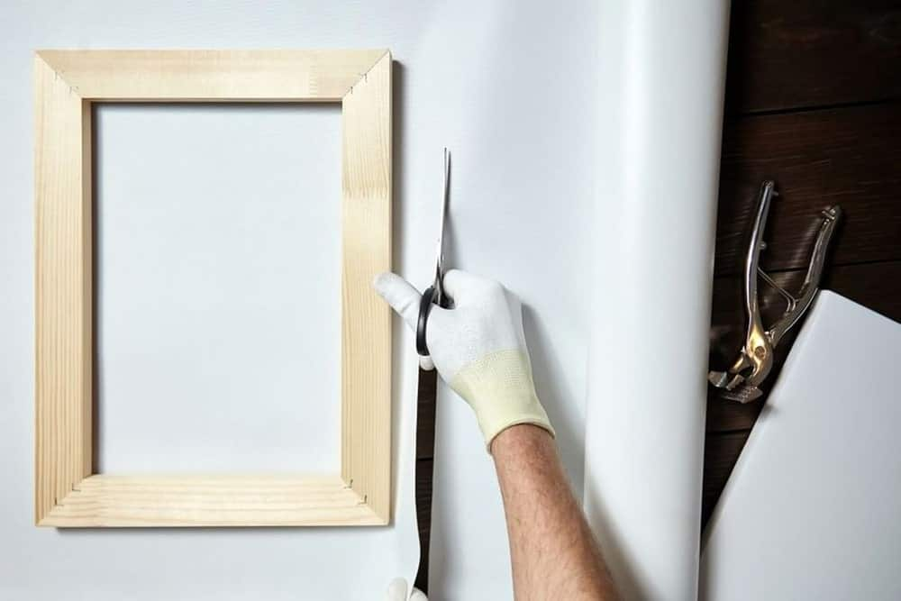 person cutting canvas fabric