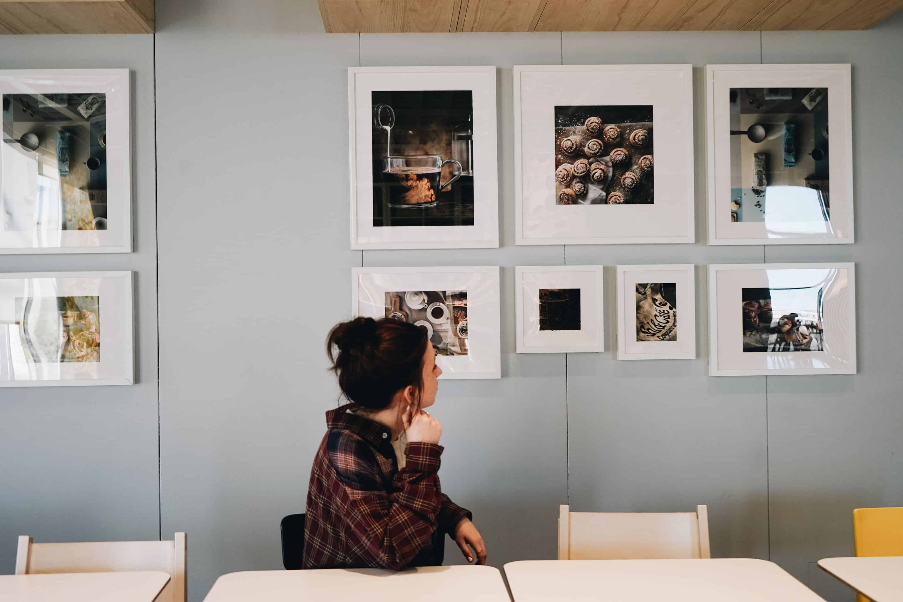 woman admiring wall artworks