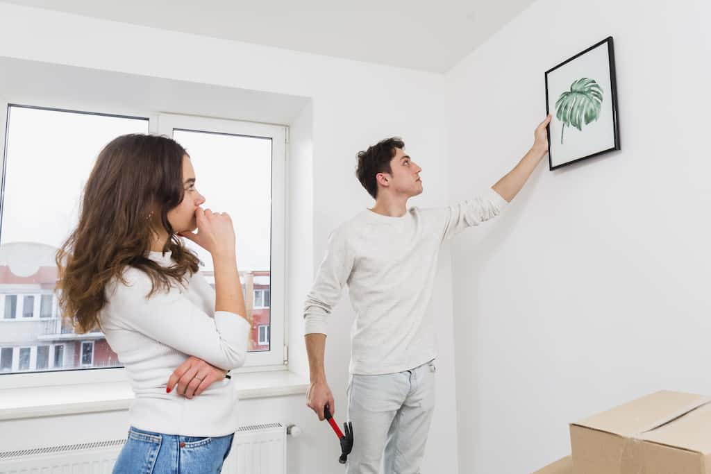a woman looking at a man who is hanging canvas art