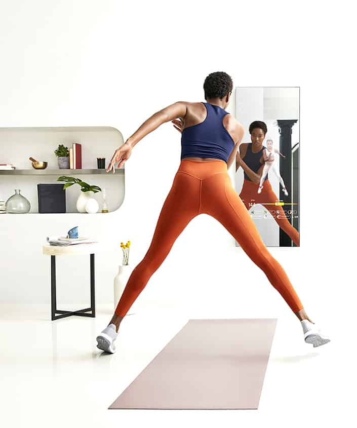 a woman working out in front of a mirror